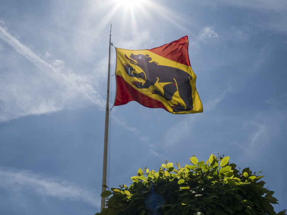 red yellow and blue flag on pole under cloudy sky during daytime