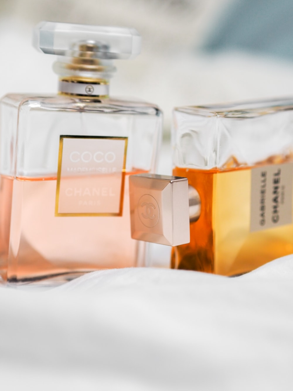 clear glass perfume bottle on white textile