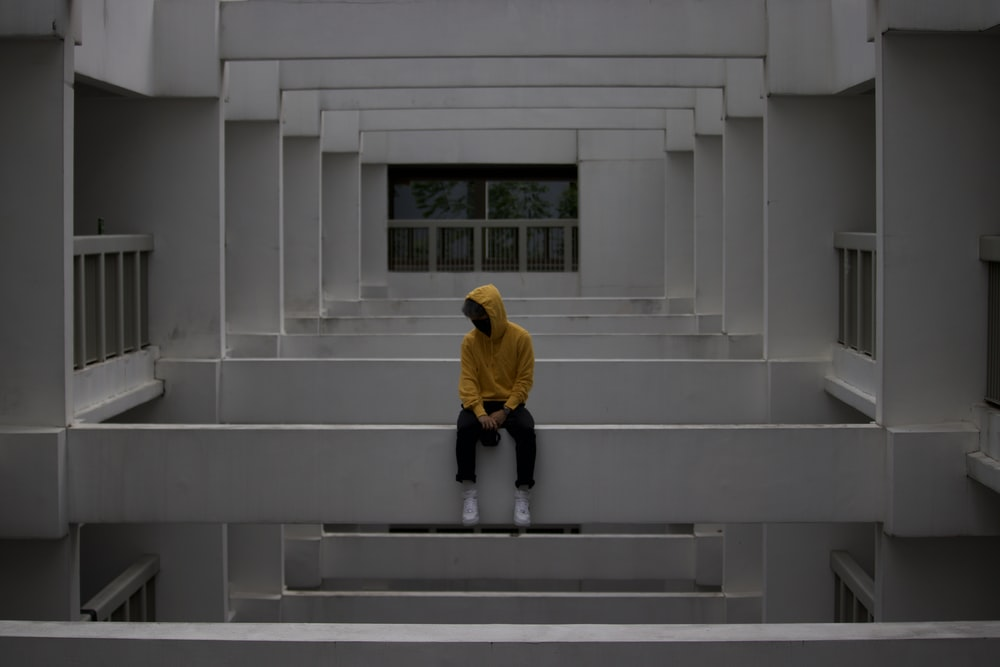 man in yellow hoodie walking on gray concrete stairs