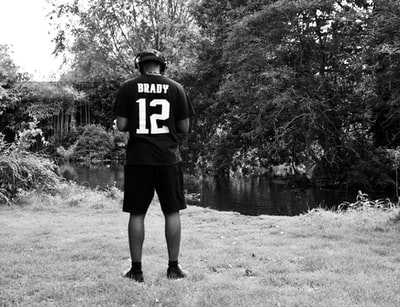 grayscale photo of man in black and white jersey shirt and shorts standing on grass field patriots zoom background