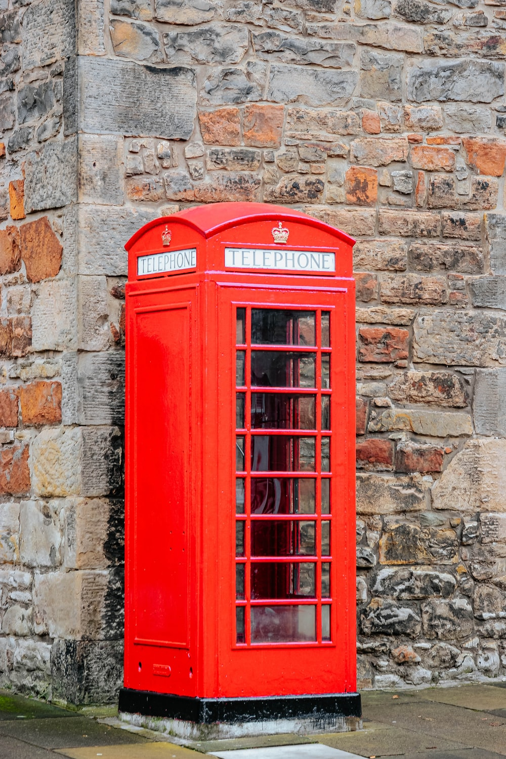 red telephone booth on brown brick wall