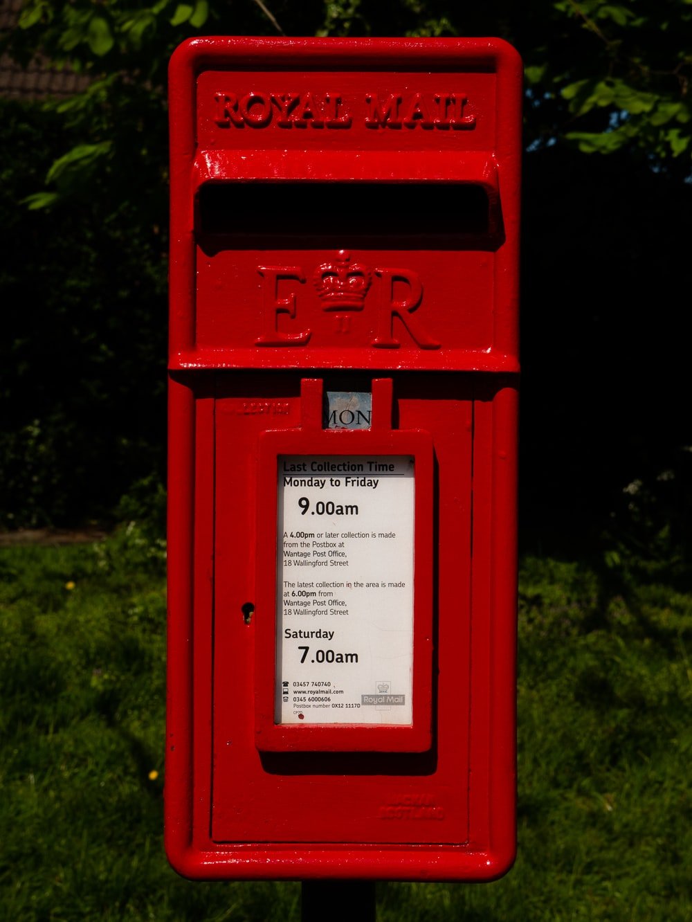 red mail box on green grass field
