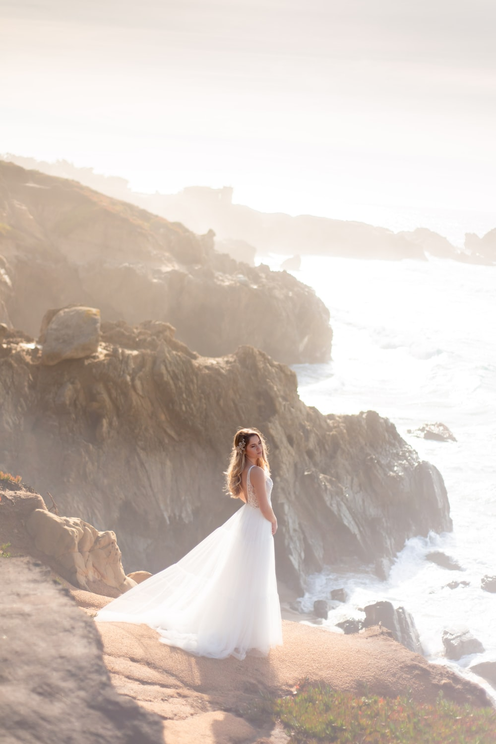 woman in white wedding dress standing on rock formation near body of water during daytime