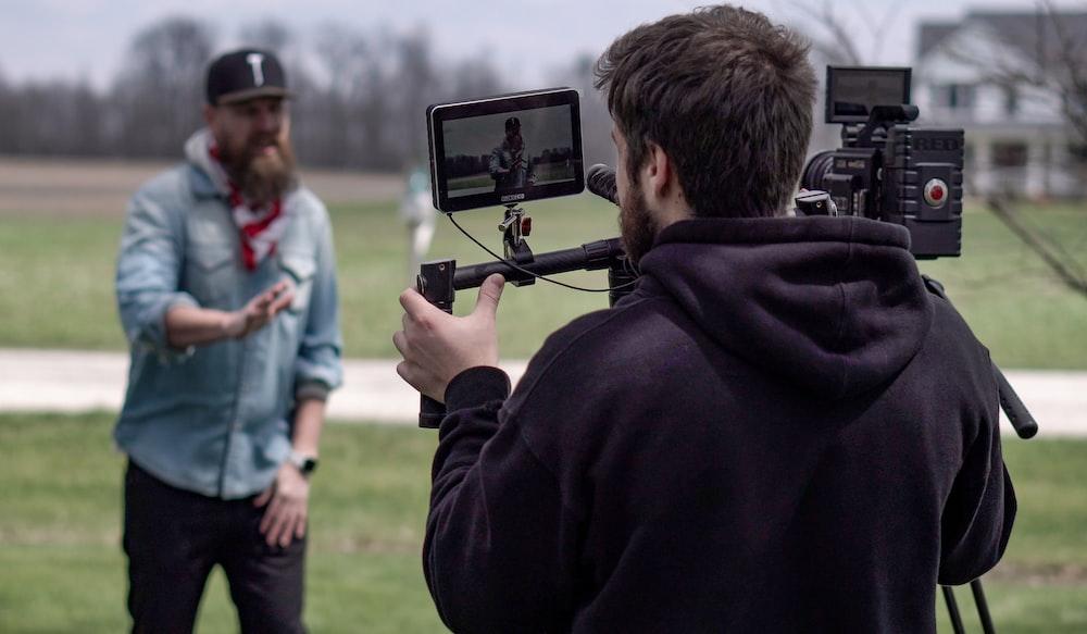 man in black hoodie holding black camera