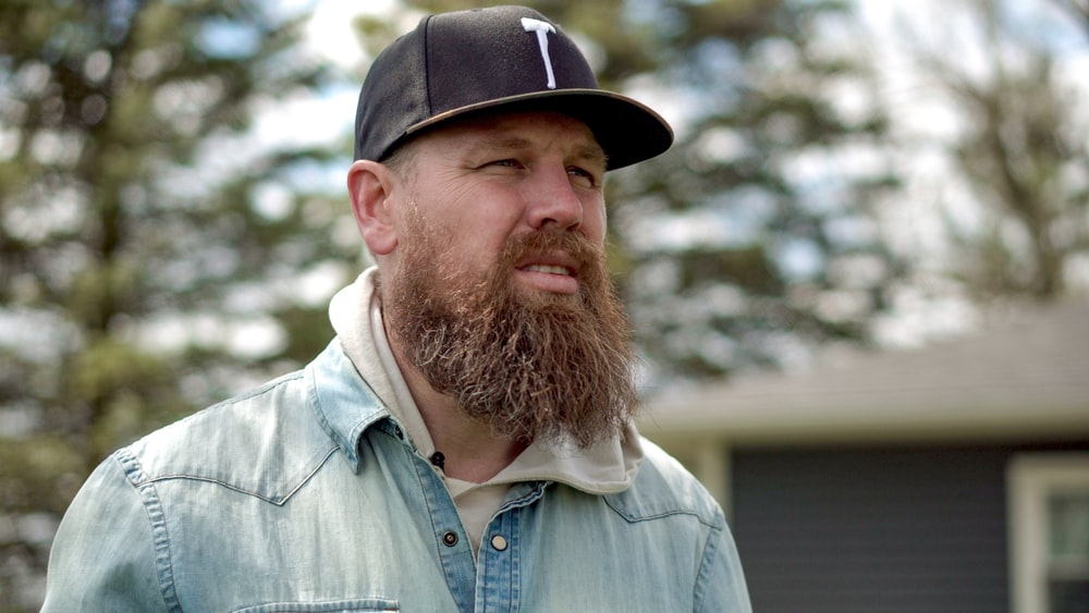 man in blue button up shirt wearing black and white cap