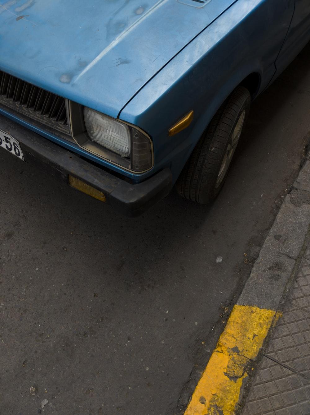 blue car on gray asphalt road