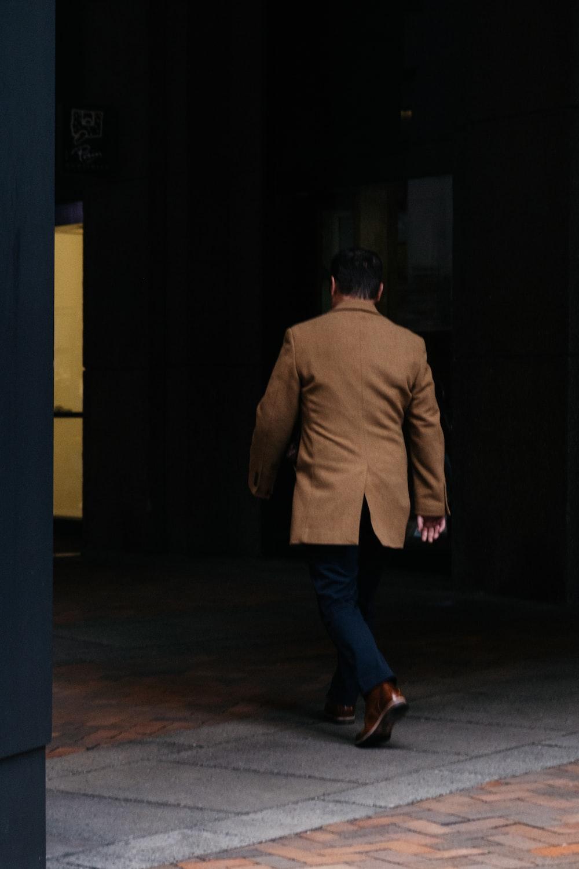 man in brown suit jacket and blue denim jeans standing on brown wooden floor