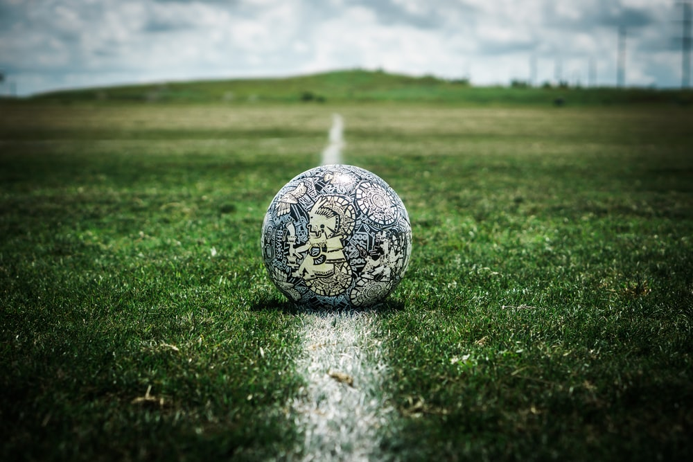 white and black soccer ball on green grass field during daytime