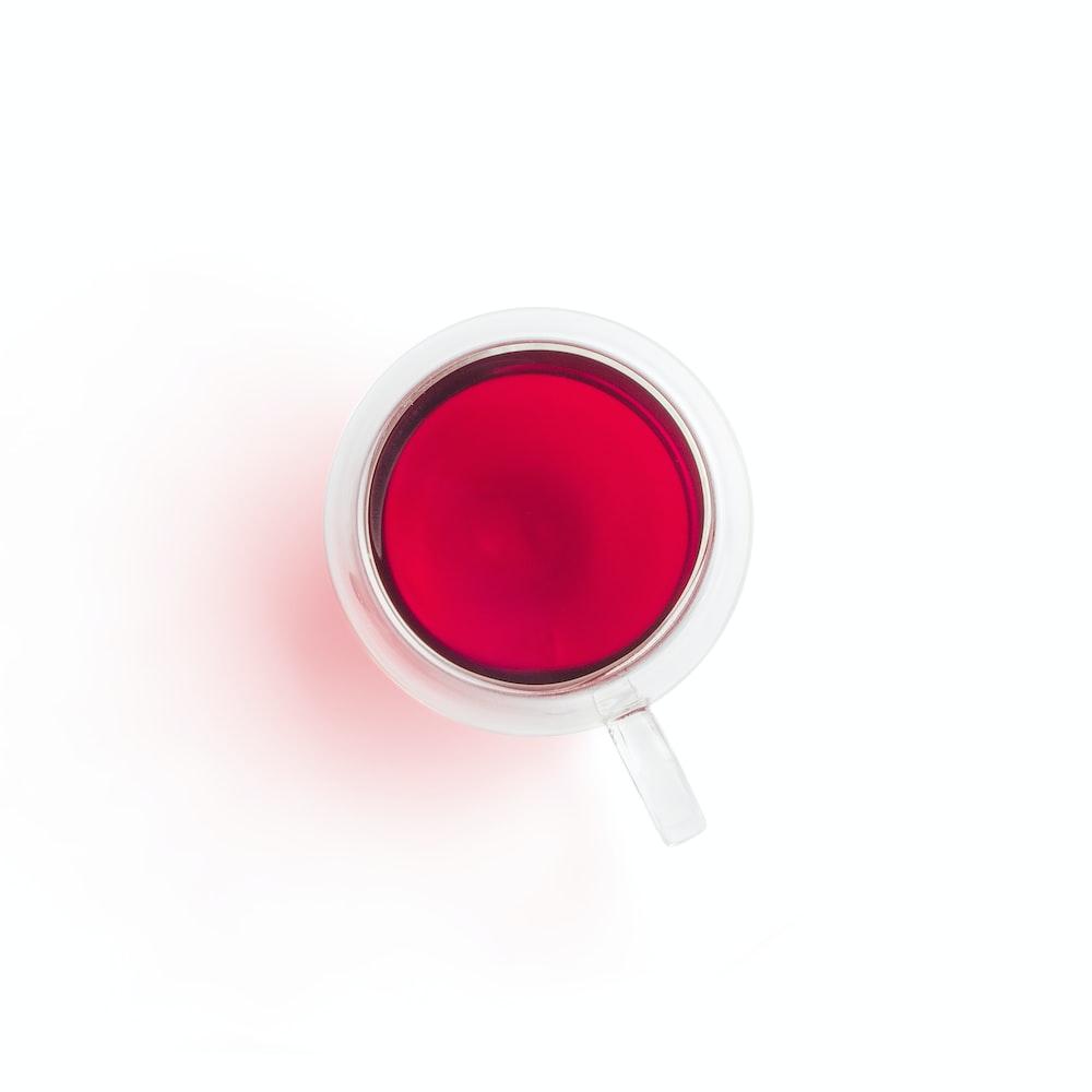 red and white ceramic mug with red liquid