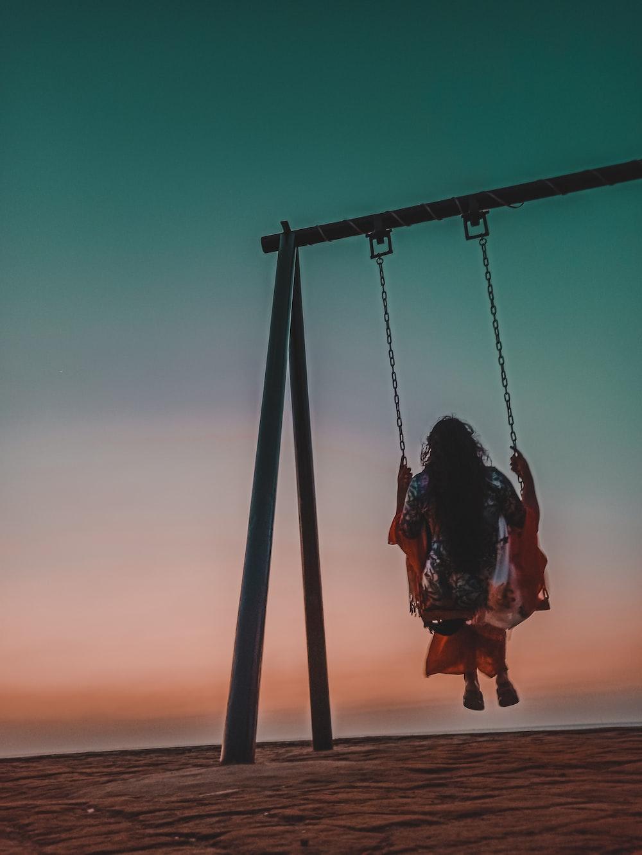 girl sitting on swing during daytime