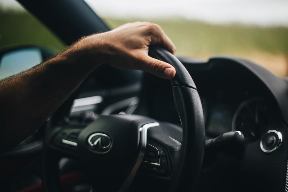 person holding black bmw steering wheel