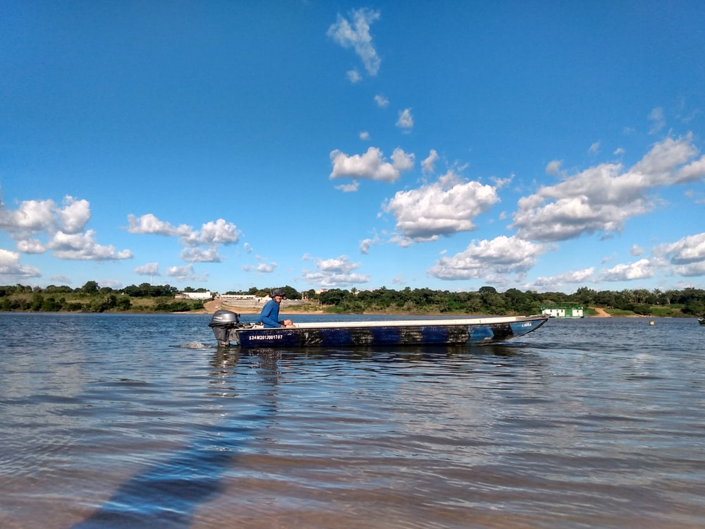 blue and white boat on sea under blue sky and white clouds during daytime