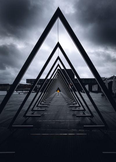 black metal bridge on sea under gray clouds