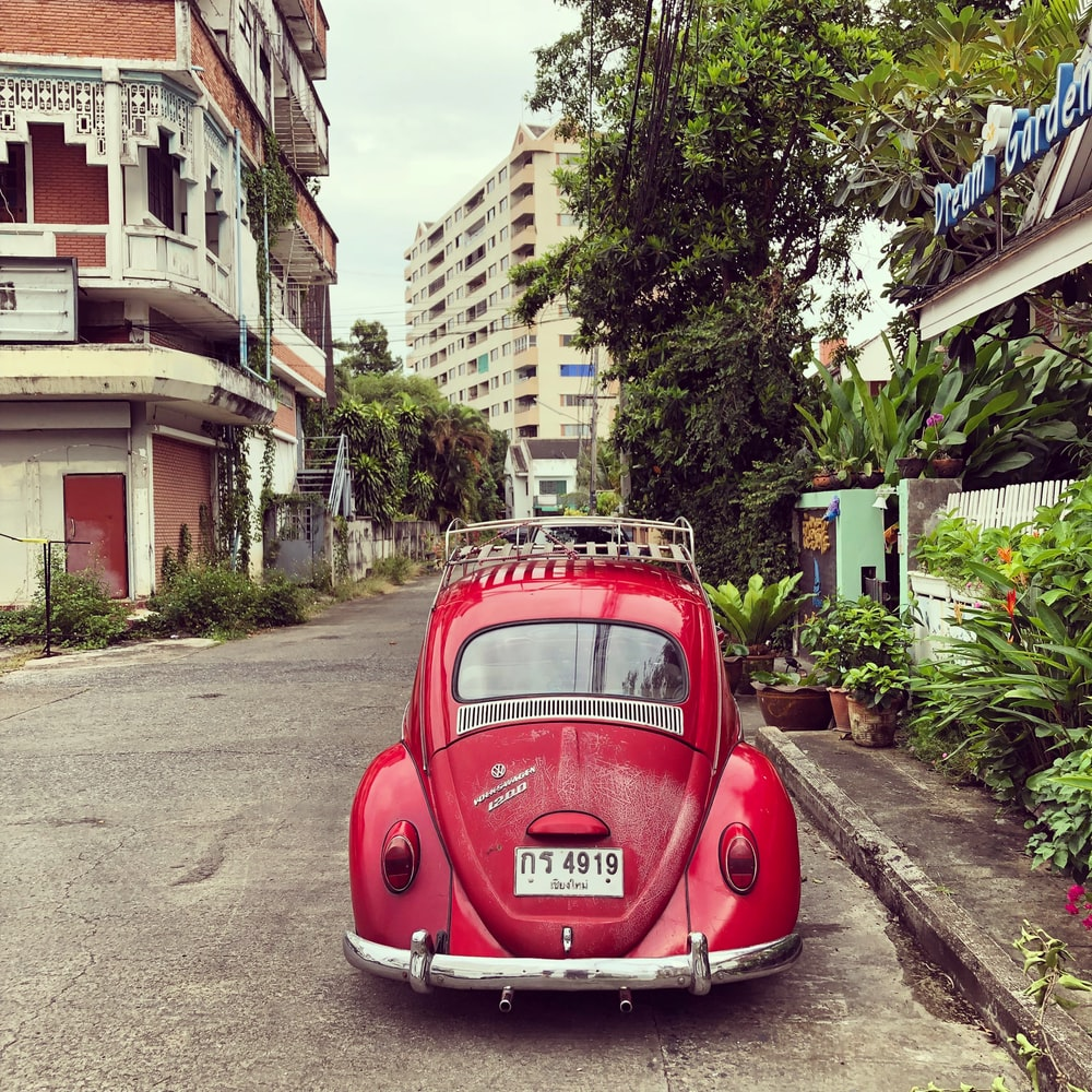 red volkswagen beetle parked on roadside near buildings during daytime