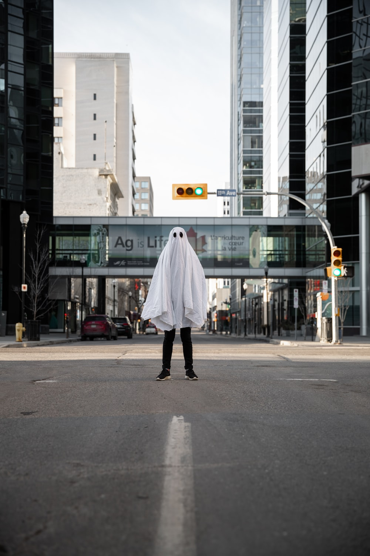 person in white coat walking on sidewalk during daytime
