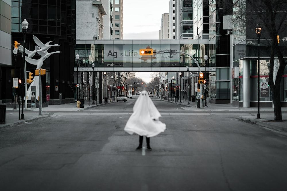woman in white dress walking on pedestrian lane during daytime