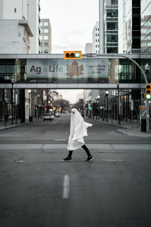 person in white robe walking on sidewalk during daytime
