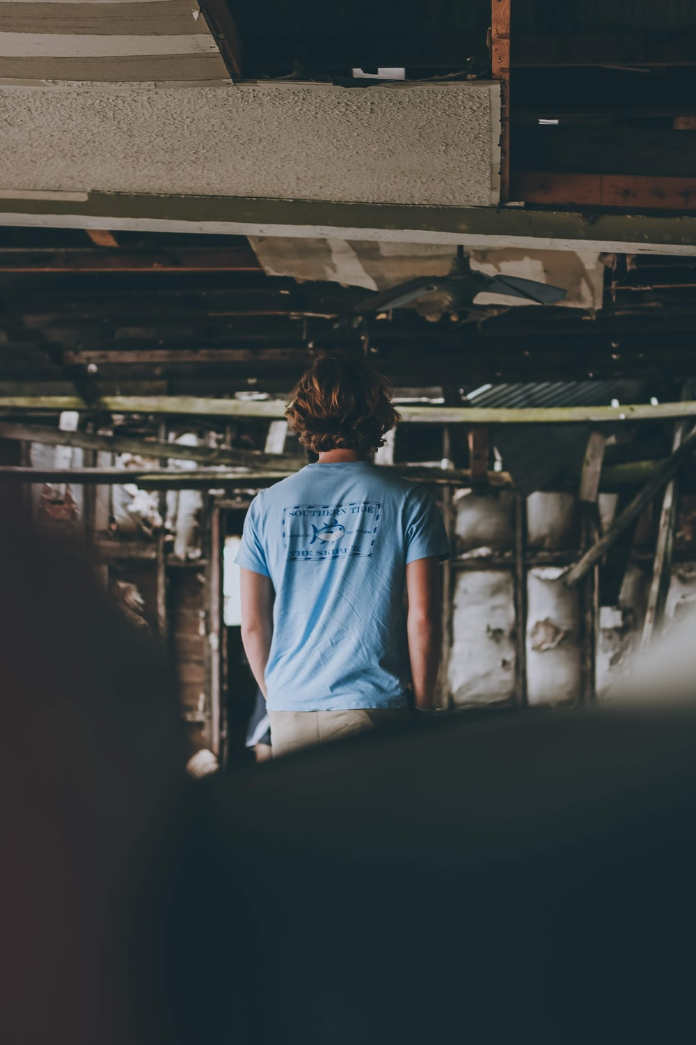 woman in blue t-shirt and blue denim jeans standing inside building