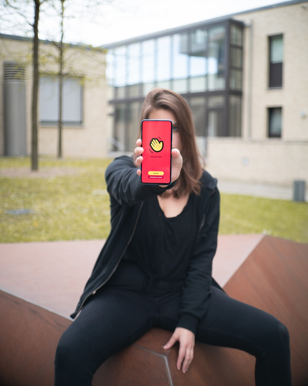 woman in black long sleeve shirt and black pants holding iphone