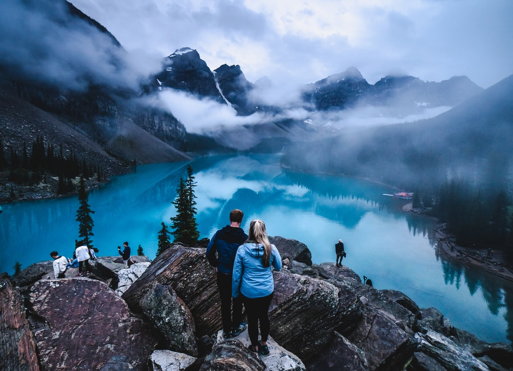 man and woman sitting on rock near lake under white clouds during daytime