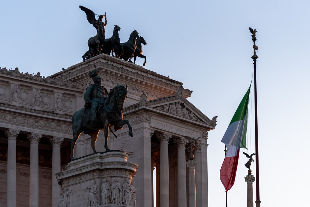 statue of man riding horse holding flag of us a during daytime
