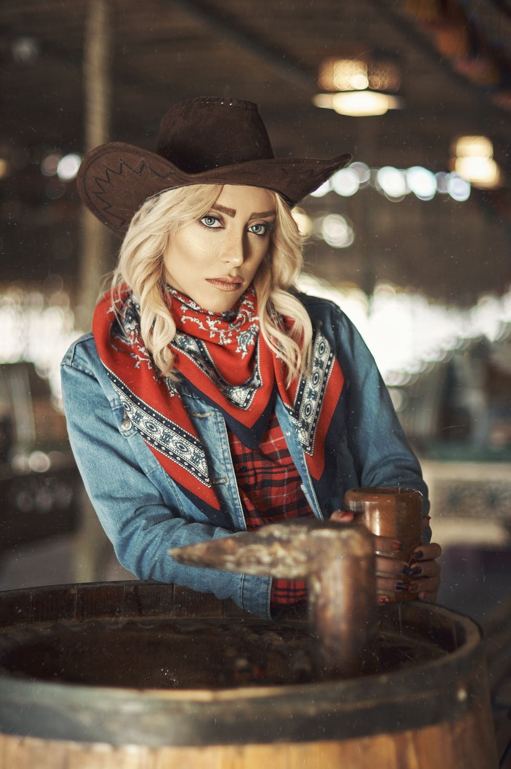 woman in blue denim jacket and black cowboy hat holding brown wooden cup