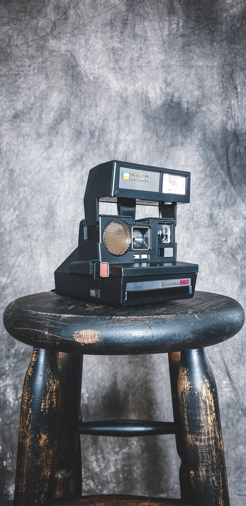 black and red polaroid camera on brown wooden seat