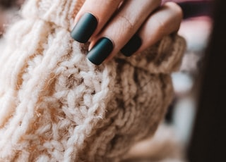 person with black manicure holding white textile