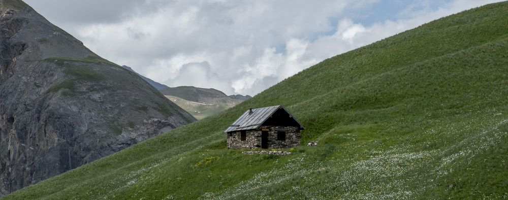 black and gray house on green grass field near mountain under white clouds during daytime