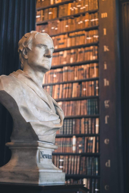 man statue near brown wooden book shelf