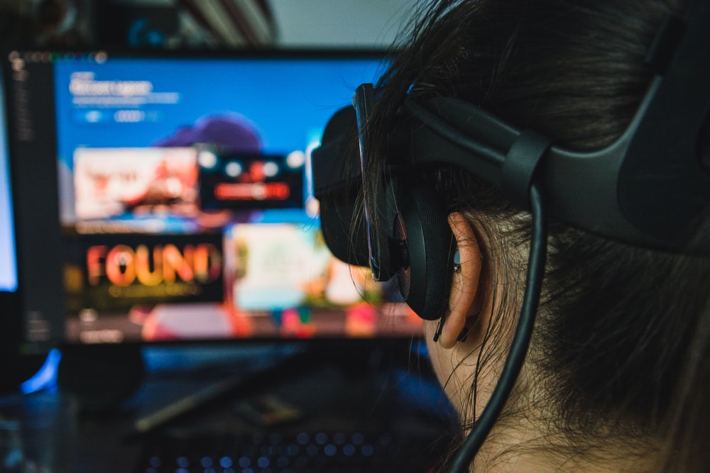 person wearing black headphones in front of black flat screen computer monitor