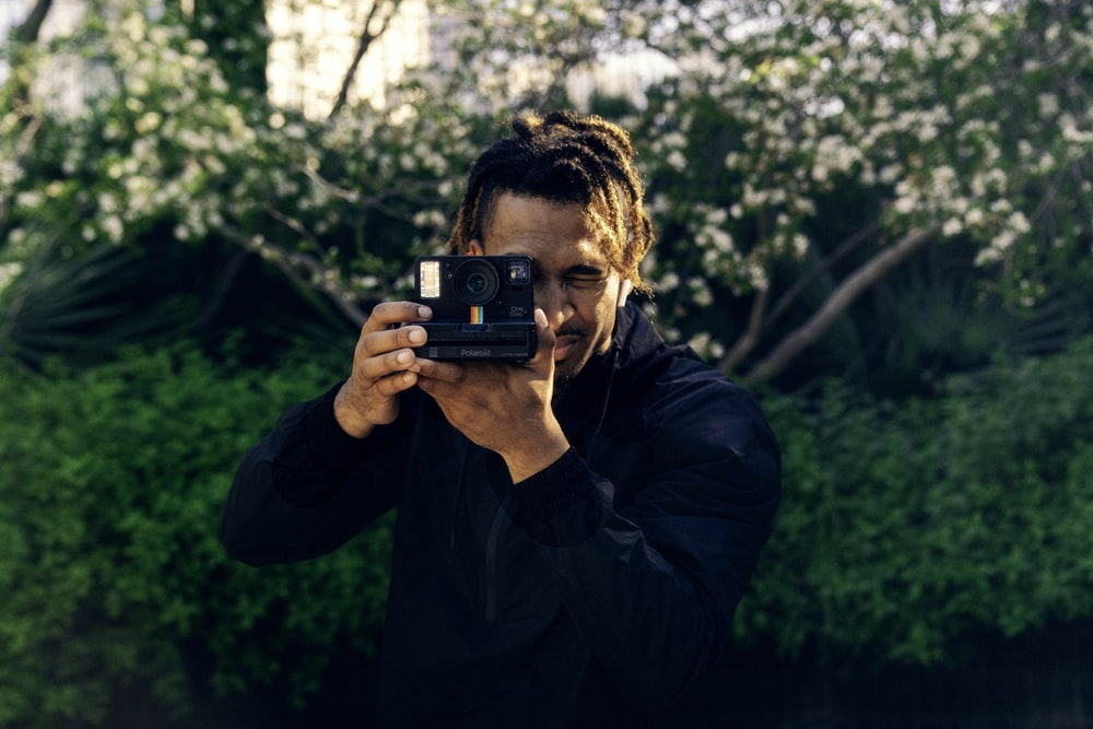 man in blue jacket holding black and red camera
