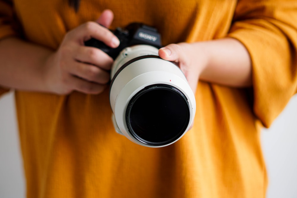 person holding white and black camera lens