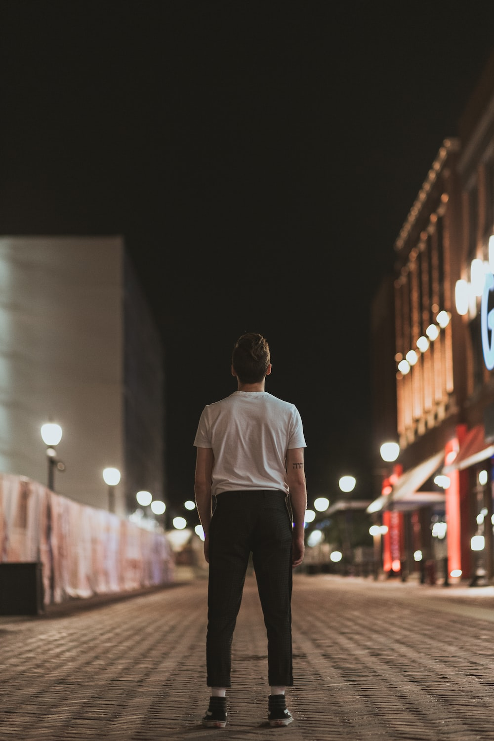 man in white crew neck t-shirt and black pants standing on street during night time