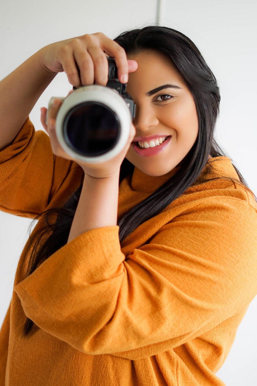 woman in orange sweater holding white ceramic mug