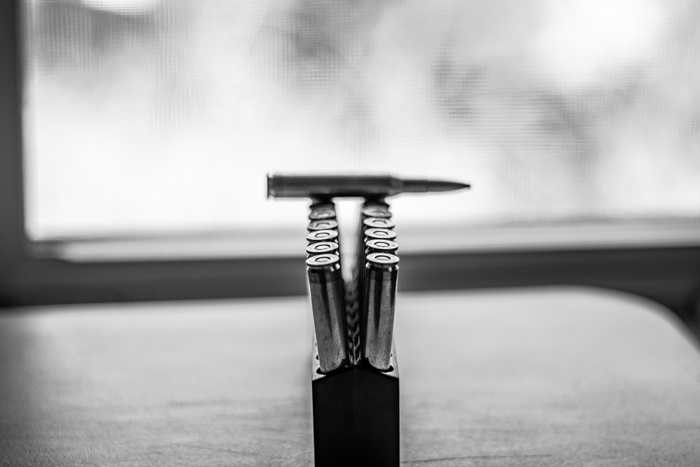 gray scale photo of two stainless steel fork on table