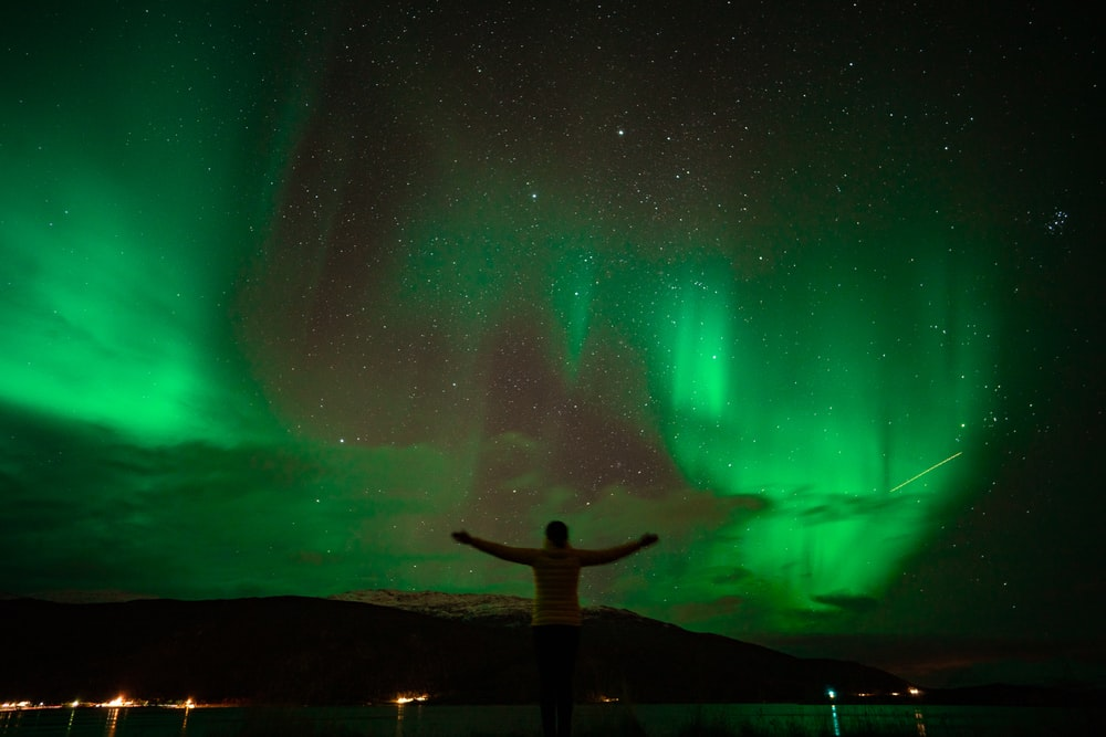 man standing on rock formation under green sky during night time