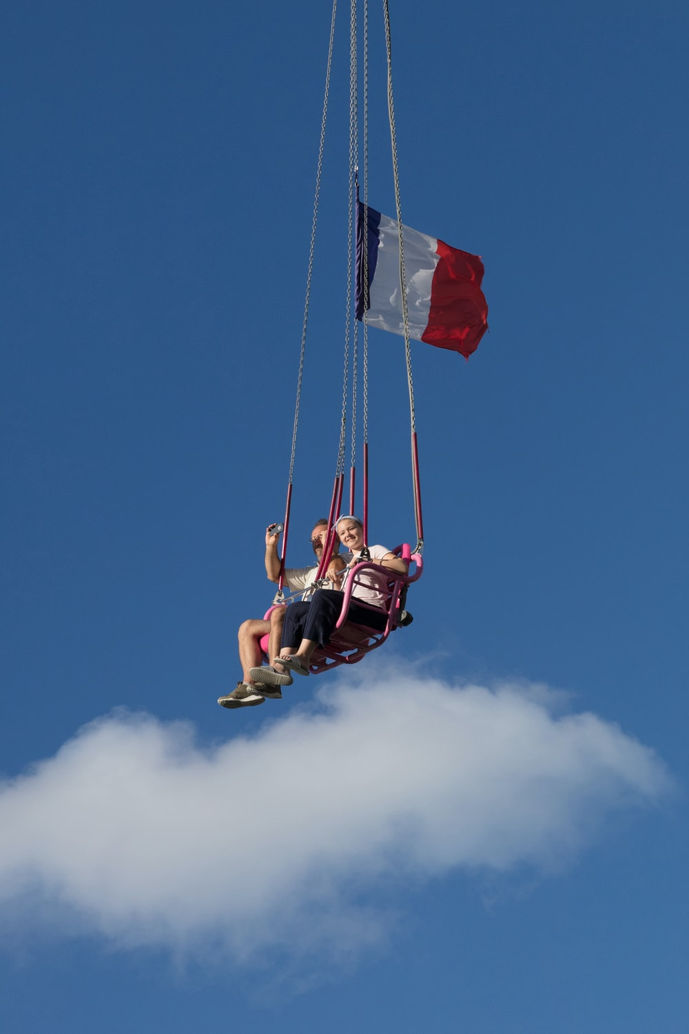 man in red shirt and black shorts riding on swing under blue sky during daytime