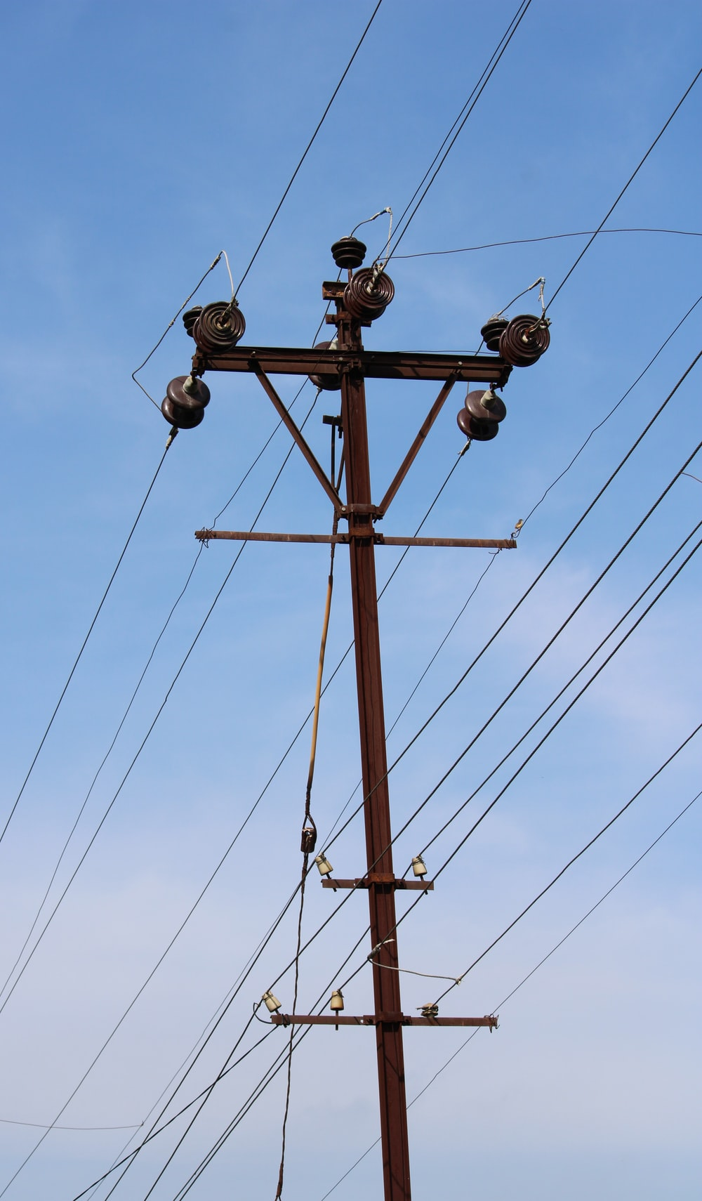 brown wooden electric post under blue sky during daytime