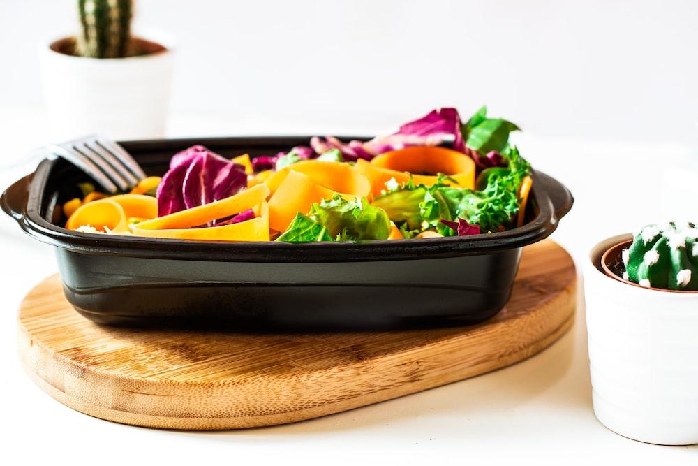black ceramic bowl with sliced fruits