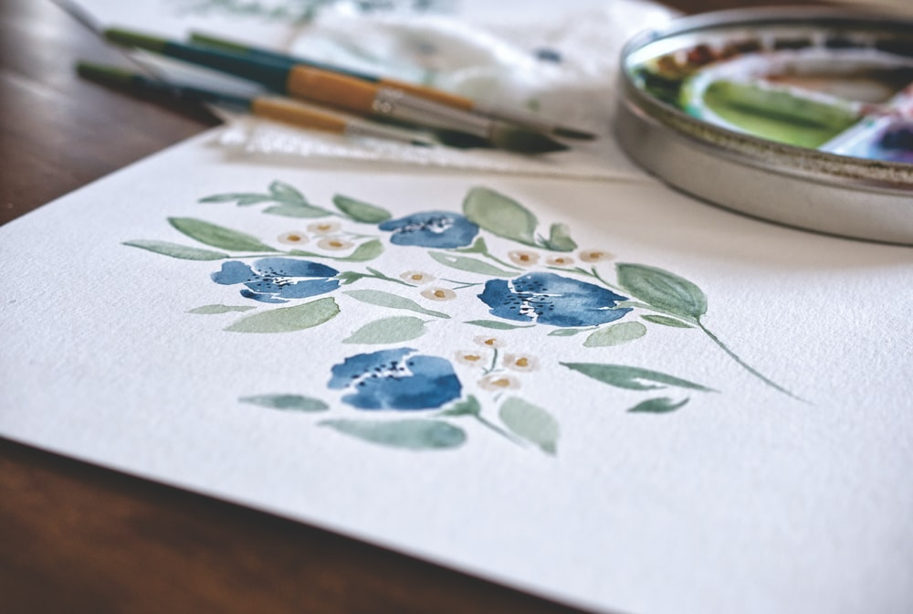 white green and blue floral ceramic plate beside white and green floral round plate