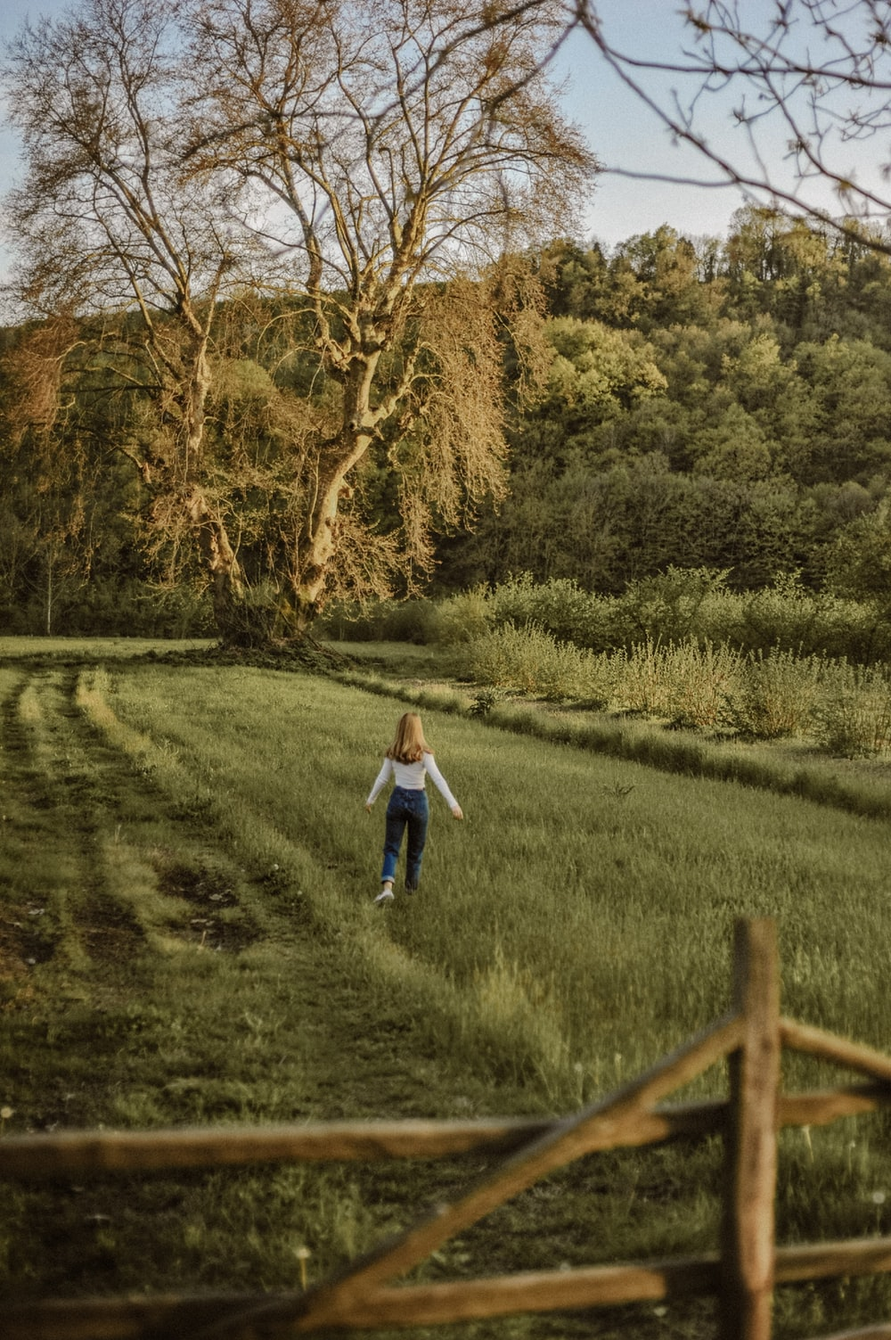 girl in white long sleeve shirt and blue denim jeans walking on green grass field during
