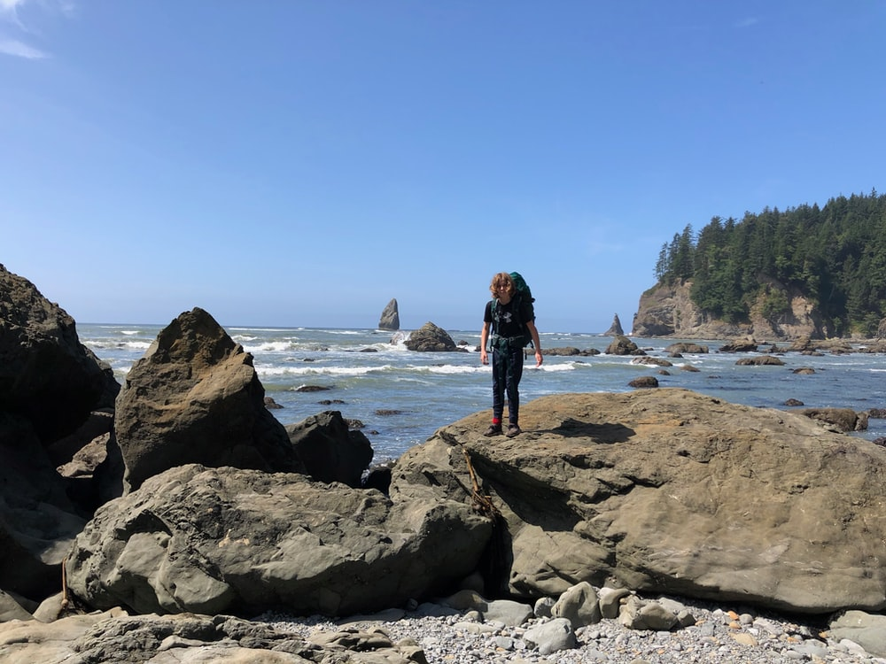 woman in black dress standing on rock formation near body of water during daytime