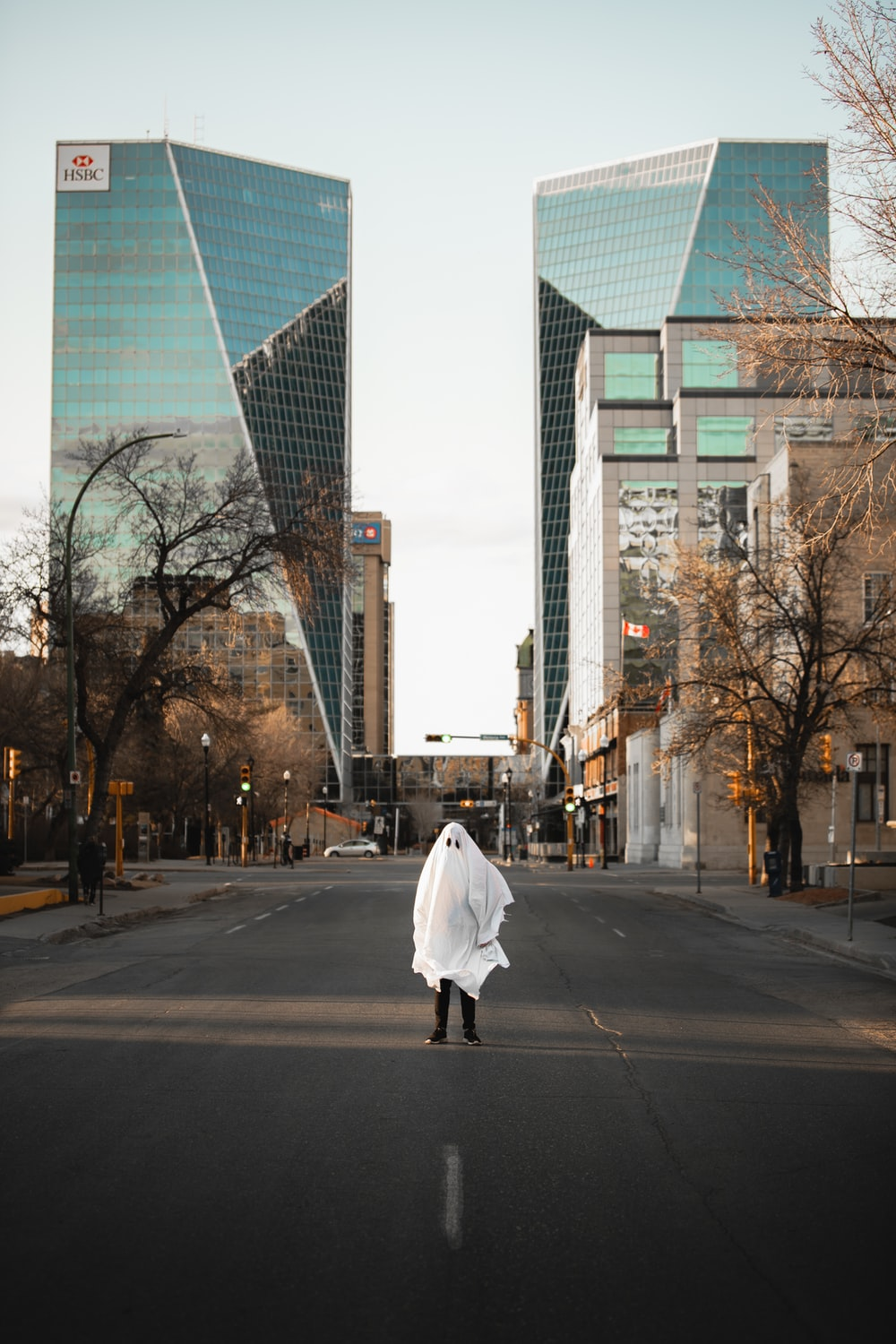 woman in white coat walking on the street during daytime