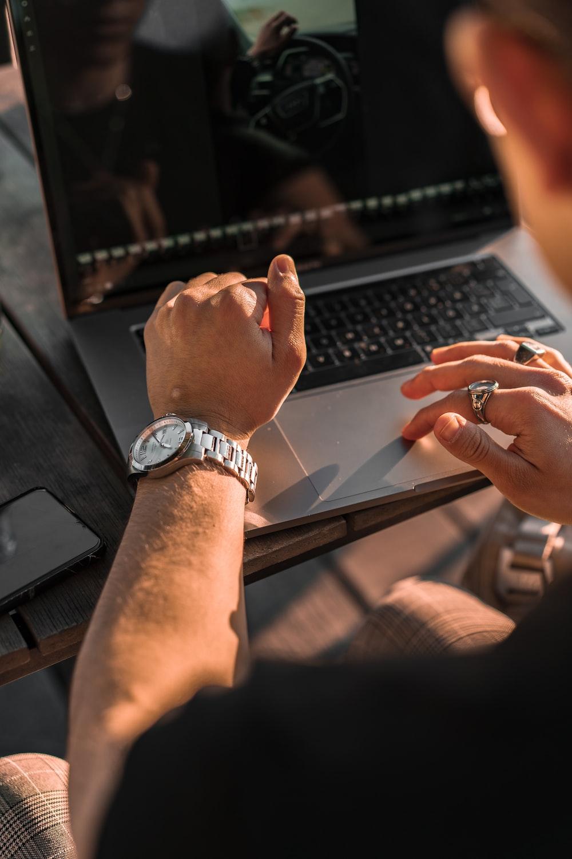 person wearing silver link bracelet round analog watch using macbook pro
