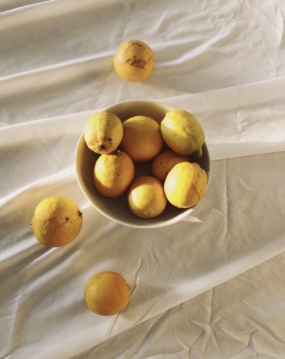yellow citrus fruits on white textile