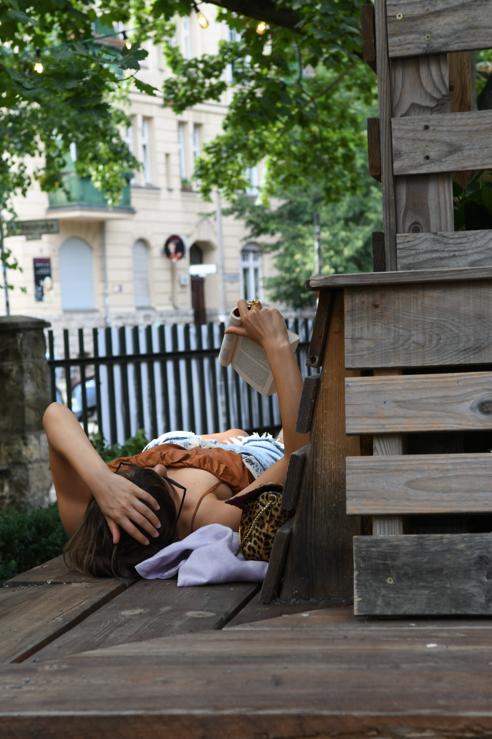 woman in white shirt and black skirt sitting on brown wooden bench