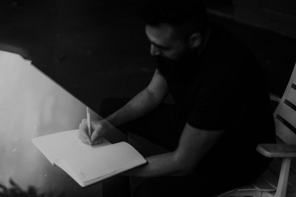 man in black t-shirt writing on white paper