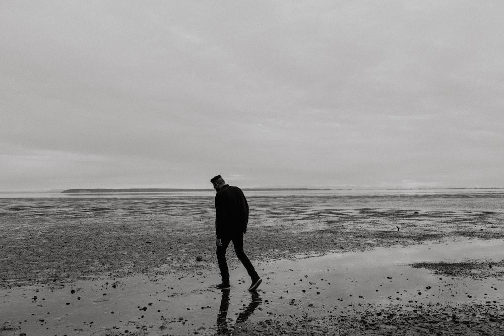 man walking on beach during daytime