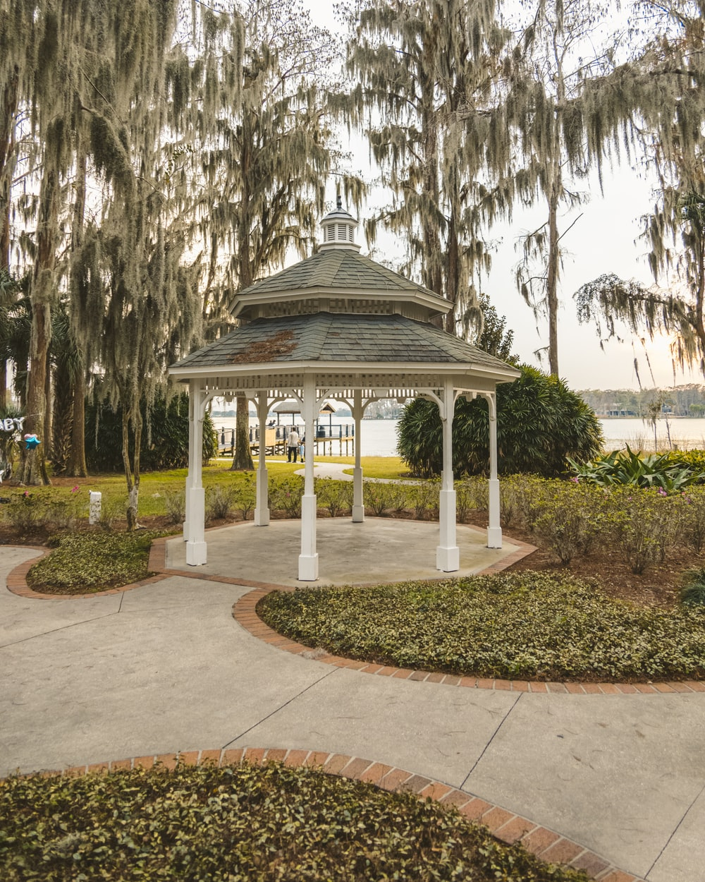 white and black gazebo surrounded by trees during daytime
